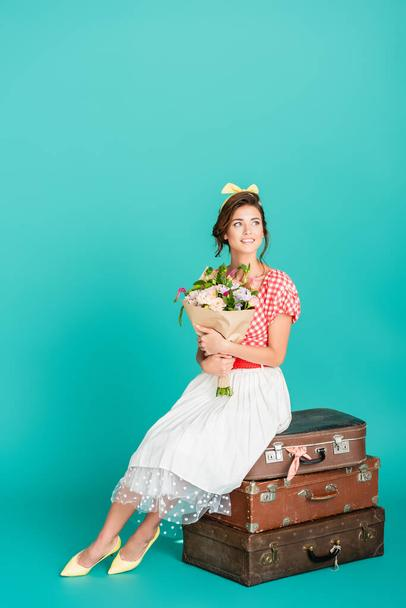 happy pin up woman with flowers sitting on retro suitcases on turquoise - Photo, Image