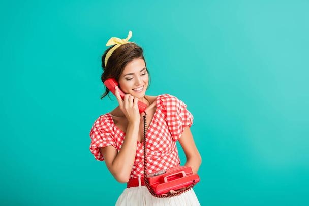 happy pin up woman talking on retro phone isolated on turquoise - Photo, Image