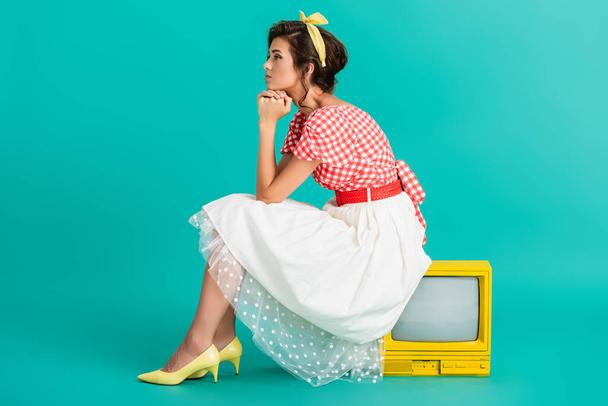 side view of dreamy pin up woman sitting on yellow vintage tv set on turquoise - Photo, Image