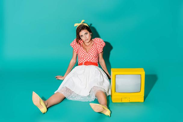 young pin up woman looking at camera while sitting on floor near yellow vintage tv on turquoise - Photo, Image