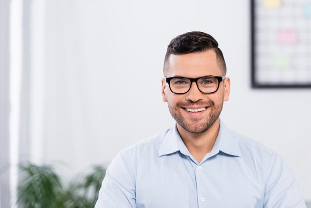 happy businessman in glasses smiling while looking at camera - Photo, Image