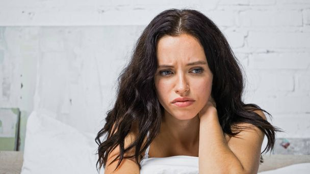 upset young woman touching neck while sitting in bedroom - Photo, Image