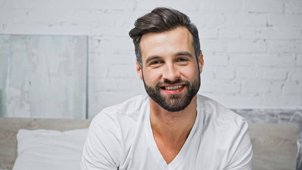 young bearded man smiling while looking at camera in bedroom - Photo, Image