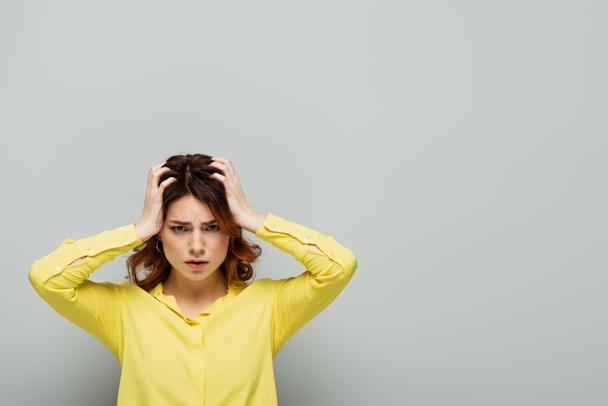 exhausted woman looking at camera while suffering from headache and touching head on grey - Photo, Image