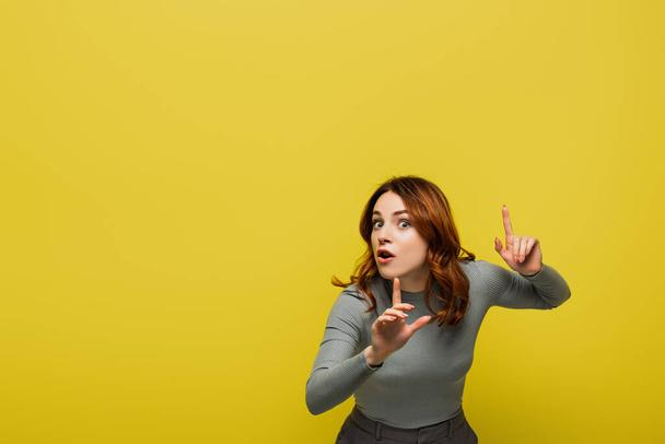 woman with curly hair and open mouth pointing with fingers isolated on yellow - Photo, Image