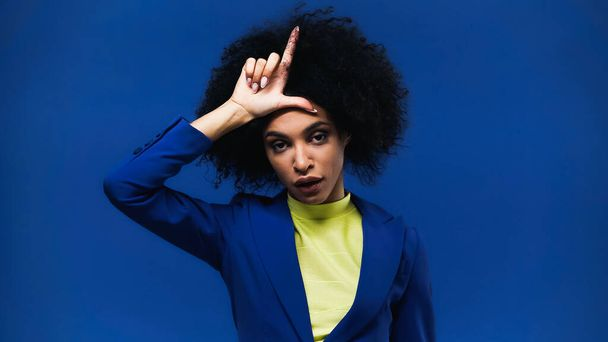 African american woman showing loser sign isolated on blue - Photo, Image