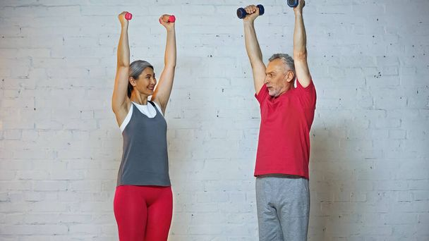 smiling asian woman looking at senior husband while training with dumbbells - Photo, Image