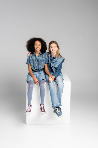 fashionable interracial kids in denim clothes sitting on white cube on grey - Photo, Image
