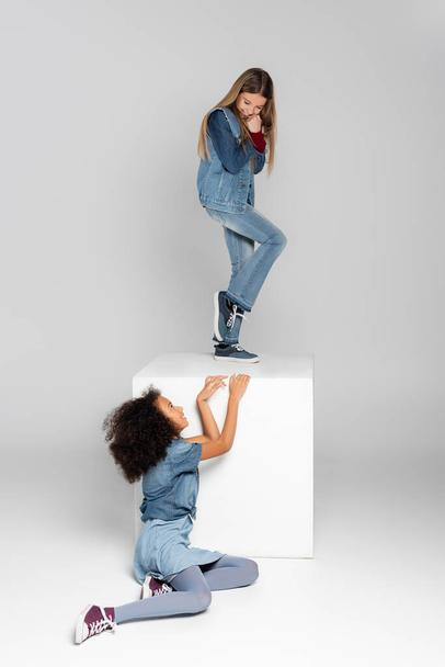 cheerful girl standing on white cube while african american girl sitting on grey - Photo, Image