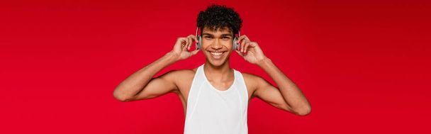 happy african american man adjusting wireless headphones isolated on red, banner - Photo, Image
