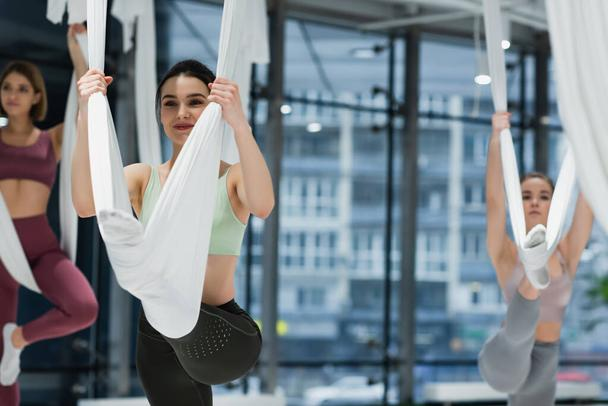 happy woman stretching on fly yoga hammock near group on blurred background - Photo, Image