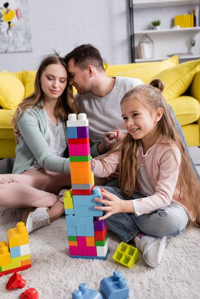 Happy girl playing colorful building blocks near parents in living room  - Photo, Image