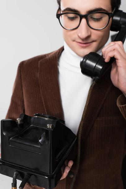 old fashioned man in brown blazer talking on retro telephone isolated on grey - Photo, Image