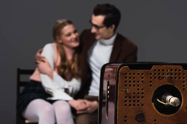 old fashioned couple embracing while watching tv isolated on dark grey, blurred background - Photo, Image