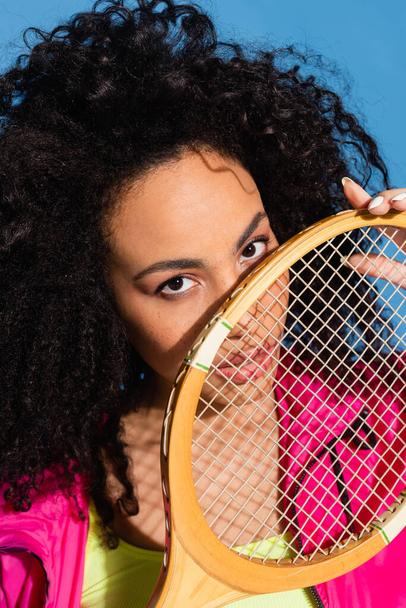 young african american woman holding tennis racket and looking at camera isolated on blue - Photo, Image