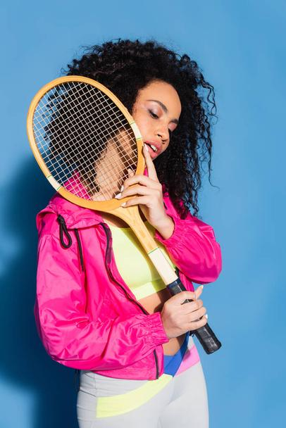 young african american woman posing with tennis racket on blue - Photo, Image