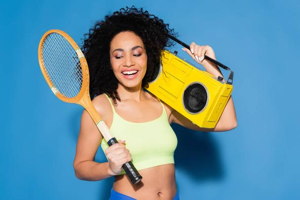 happy african american woman holding boombox and tennis racket on blue - Photo, Image