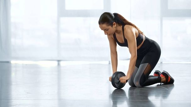 sweaty young sportswoman training with ab wheel in gym - Photo, Image