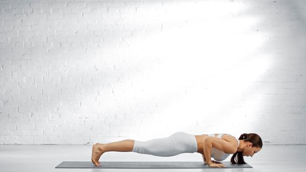 Side view of woman doing four-limbed staff pose on yoga mat  - Photo, Image