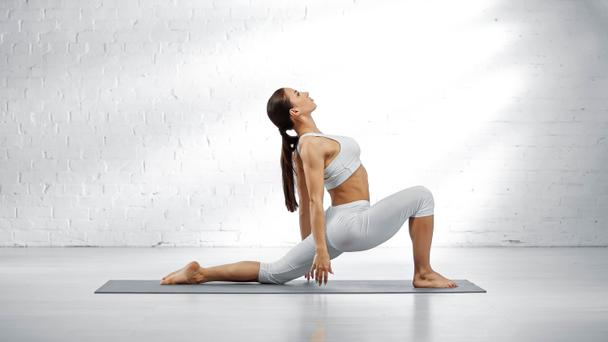 Side view of brunette woman standing in yoga pose  - Photo, Image