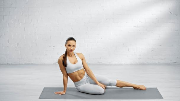 Young woman looking at camera on yoga mat  - Photo, Image