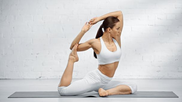 Fit woman sitting in yoga pose on mat  - Photo, Image