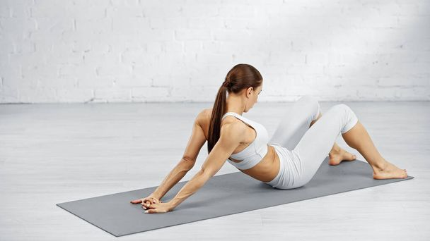 Young woman stretching arms on yoga mat at home  - Photo, Image