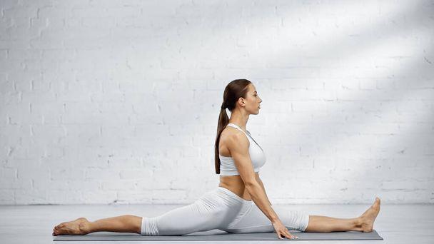 Young woman doing split on yoga mat  - Photo, Image