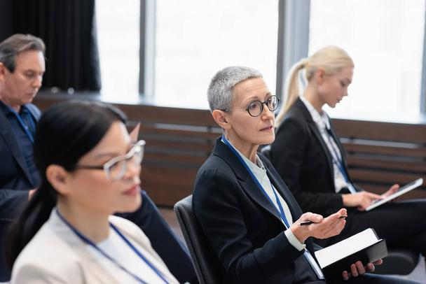 Mature businesswoman with pen and notebook talking during conference  - Photo, Image