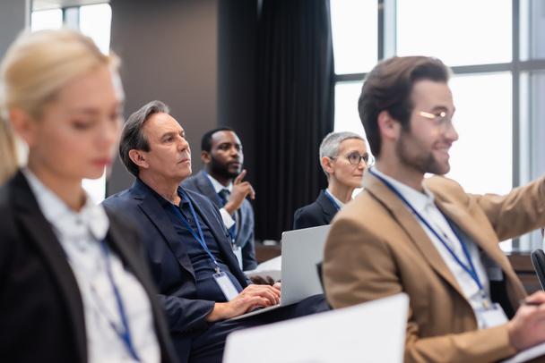 Mature businessman using laptop during seminar near interracial business people  - Photo, Image