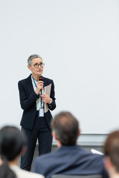Businesswoman with paper folder and microphone talking during seminar  - Photo, Image