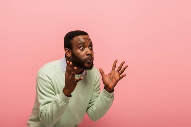 Amazed african american man looking away isolated on pink  - Photo, Image