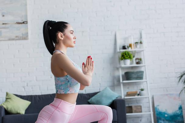 side view of young sportswoman training with praying hands at home - Photo, Image