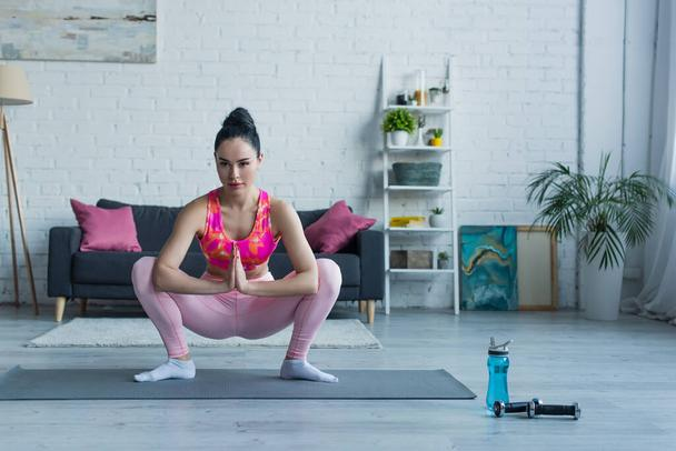 young woman in sportswear training in squatting pose with praying hands - Photo, Image