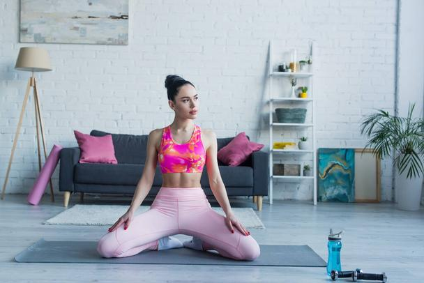 brunette woman in sports bra and leggings looking away while sitting on fitness mat - Photo, Image