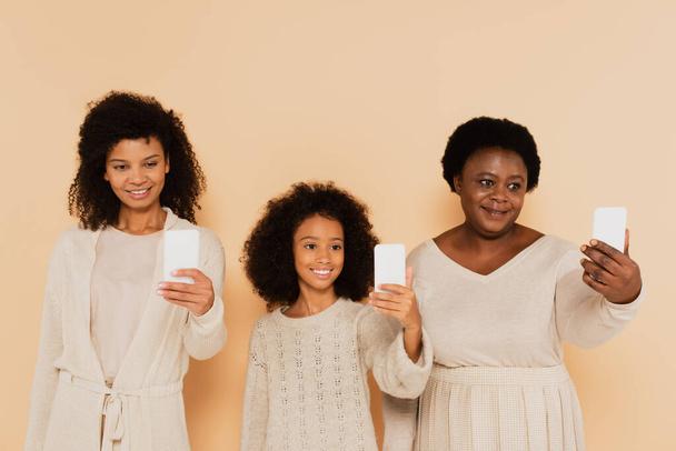 Afrikanisch-amerikanische Tochter, Enkelin und Großmutter machen Selfies auf Mobiltelefonen auf beigem Hintergrund - Foto, Bild