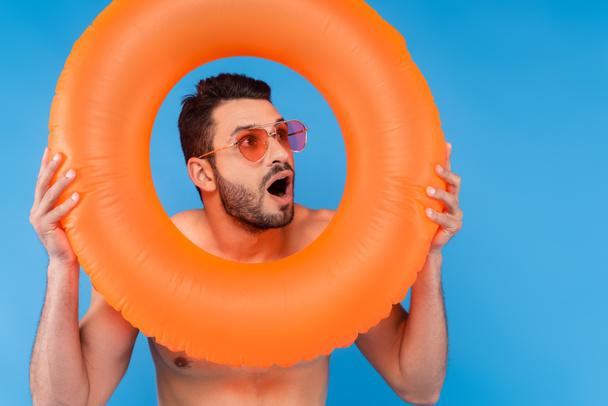 Возбужденный мужчина в солнечных очках с надувным кольцом, изолированным на голубом  - Фото, изображение