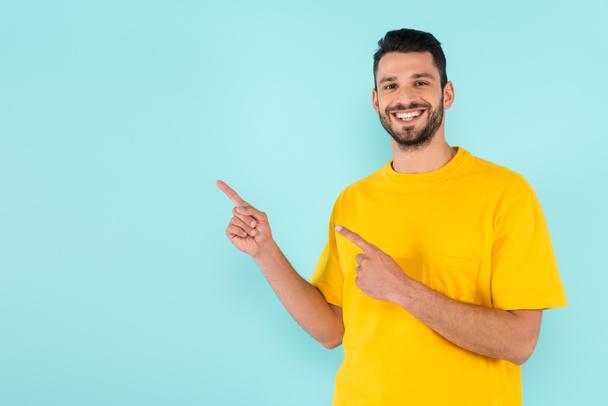 Улыбающийся мужчина, указывающий пальцами на синий  - Фото, изображение