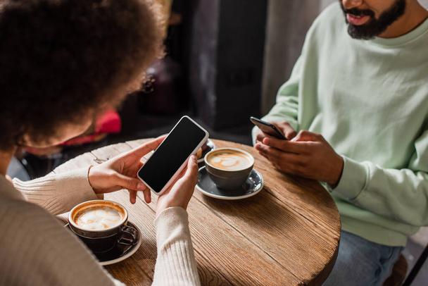 Смартфон с чистым экраном в руках африканской американки, сидящей рядом с парнем, и кофе в кафе  - Фото, изображение