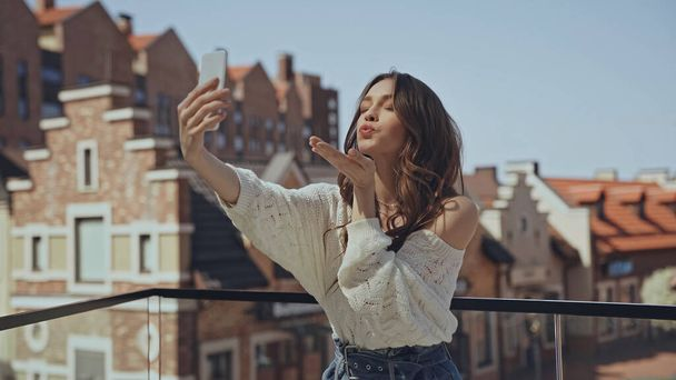 happy young woman taking selfie and sending air kiss  - Photo, Image