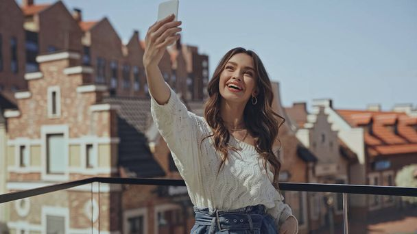 amazed young woman taking selfie near blurred buildings  - Photo, Image