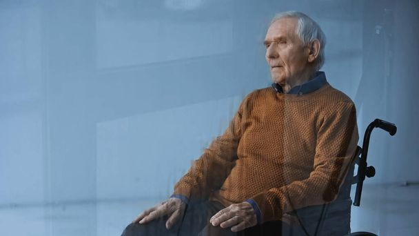 thoughtful senior man in wheelchair looking away on grey background - Photo, Image