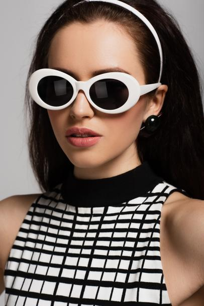 trendy young model in sunglasses and headband isolated on grey  - Photo, Image