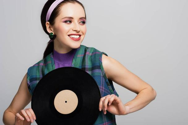 smiling woman in headband holding vintage vinyl disc isolated on grey - Photo, Image