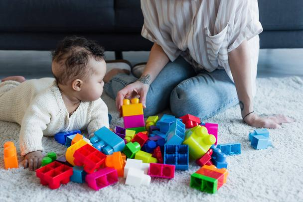 african american baby girl crawling on floor near mother and colorful building blocks - Photo, Image