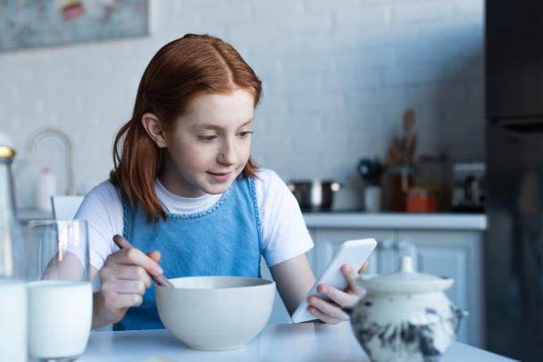 рыжеволосая девушка использует смартфон во время завтрака - Фото, изображение