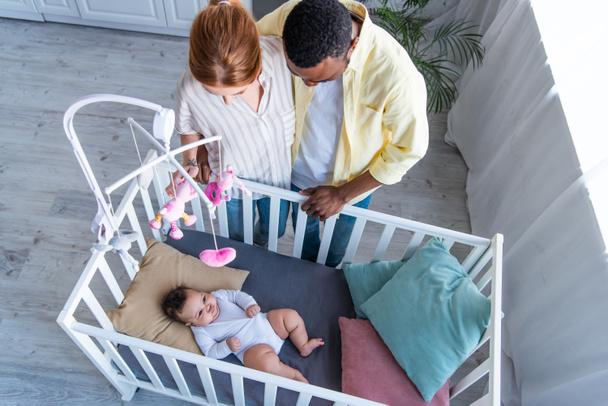 вид сверху на межрасовую пару, стоящую рядом с ребенком, лежащим в кроватке - Фото, изображение