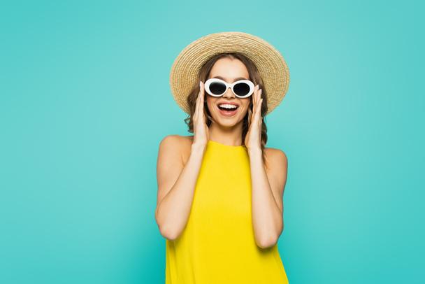 Позитивная женщина в соломенной шляпе и солнечных очках, изолированных на голубом  - Фото, изображение