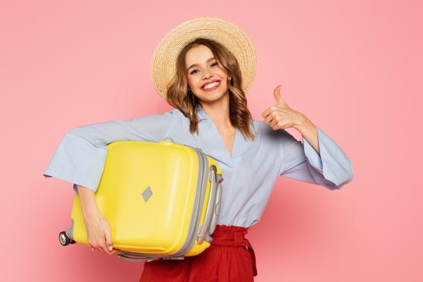 Веселая женщина в солнечной шляпе держит чемодан и показывает, как жест изолирован на розовый  - Фото, изображение