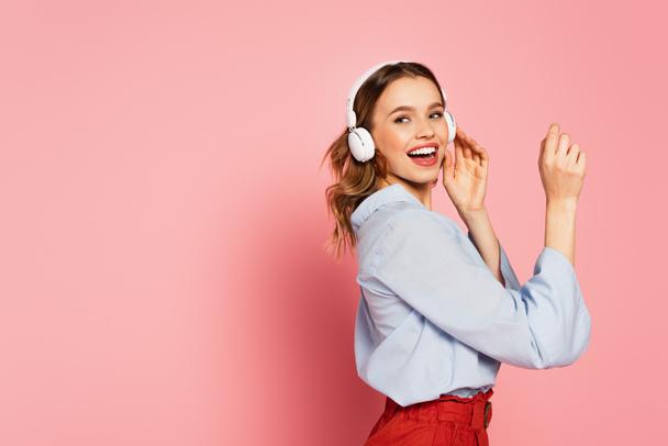 Позитивная женщина в наушниках смотрит в сторону на розовом фоне  - Фото, изображение